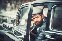 Αναδρομικός-οδηγός στο εκλεκτής ποιότητας αυτοκίνητο στο υπαίθριο υπόβαθρο στοκ εικόνες