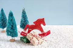Αναδρομικό άλογο παιχνιδιών Χριστουγέννων με τα δέντρα πεύκων και τα κιβώτια δώρων στον ξύλινο πίνακα που καλύπτεται με το χιόνι Στοκ φωτογραφία με δικαίωμα ελεύθερης χρήσης