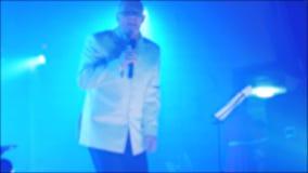Αναδρομικό θολωμένο συναυλία υπόβαθρο μουσικής Πρεσβύτερος ένας ηληκιωμένος που τραγουδά στο μικρόφωνο σε αργή κίνηση βίντεο Αναδ φιλμ μικρού μήκους