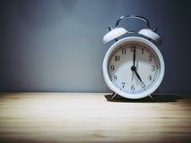 Αναδρομικό ξυπνητήρι με το ρολόι πέντε ο ` Παλαιά φιλτραρισμένη ύφος φωτογραφία στοκ φωτογραφία με δικαίωμα ελεύθερης χρήσης