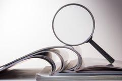 Αναζήτηση με την ενίσχυση - γυαλί, που ψάχνει τις πληροφορίες στα βιβλία, σχεδιαγράμματα, περιοδικά Επιθεώρηση λογιστικού ελέγχου στοκ φωτογραφία με δικαίωμα ελεύθερης χρήσης