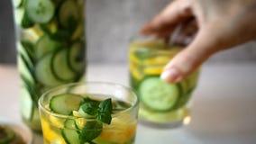 Αναζωογονώντας θερινό ποτό με το λεμόνι, την πιπερόριζα, το φρέσκες αγγούρι και τη μέντα Το χέρι της γυναίκας βάζει το γυαλί με τ απόθεμα βίντεο