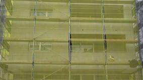 Ανακαίνιση προσόψεων οικοδόμησης, παλαιά αναδημιουργία σπιτιών, επισκευή Ικρίωμα μπροστά από την οικοδόμηση της πρόσοψης που καλύ απόθεμα βίντεο