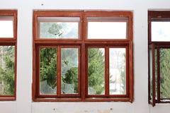 Ανακαινισμένο ξύλινο πλαίσιο παραθύρων με τα σπασμένα δέντρα γυαλιού και πεύκων στο υπόβαθρο Στοκ φωτογραφία με δικαίωμα ελεύθερης χρήσης