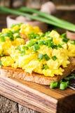 Ανακατωμένα αυγά με το πράσινο κρεμμύδι στις φρυγανιές Στοκ Φωτογραφία