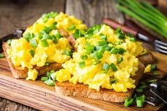 Ανακατωμένα αυγά με το πράσινο κρεμμύδι στις φρυγανιές Στοκ φωτογραφία με δικαίωμα ελεύθερης χρήσης