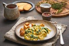 Ανακατωμένα αυγά με το σπανάκι, φλυτζάνι του τσαγιού στο σκοτεινό καφετί υπόβαθρο Το πρόγευμα με την παν-τηγανισμένη ομελέτα, πλά στοκ φωτογραφίες