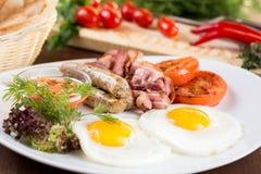 Ανακατωμένα πρόγευμα αυγά με τα βαυαρικά λουκάνικα και το μπέϊκον Στοκ Φωτογραφία