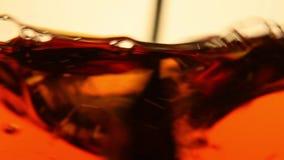 Ανακατώνοντας και whirling μαύρο τσάι στο γυαλί κοντά επάνω απόθεμα βίντεο