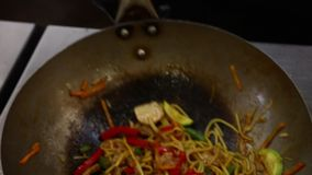 Ανακατώστε τα τηγανίζοντας νουντλς, κρέας, λαχανικά στο τηγάνι wok απόθεμα βίντεο