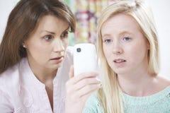 Ανακουφίζοντας κόρη μητέρων που φοβερίζεται από το μήνυμα κειμένου στοκ εικόνες