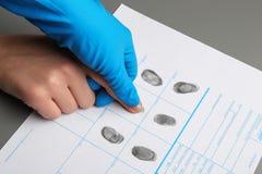Ανακριτής που παίρνει τα δακτυλικά αποτυπώματα του υπόπτου στον πίνακα Εγκληματική πείρα στοκ εικόνα