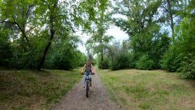 ανακυκλώνοντας πάρκο Κορίτσι που οδηγά ένα ποδήλατο σε ένα δασικό ίχνος κίνηση αργή απόθεμα βίντεο