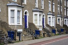 Ανακυκλώνοντας δοχεία και ποδήλατα, πάροδος ποδηλάτων, κατοικημένη οδός, Καίμπριτζ, Αγγλία στοκ εικόνα