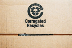 Ανακυκλώστε το σημάδι που απομονώνεται στο χαρτόνι Στοκ Φωτογραφία
