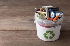 Ανακύκλωσης δοχείο μπαταριών με το παλαιό στοιχείο στον ξύλινο πίνακα στοκ εικόνες