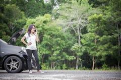 Αναλύω αυτοκίνητο και ασιατική γυναίκα που καλούν το μηχανικό αυτοκινήτων Στοκ εικόνα με δικαίωμα ελεύθερης χρήσης