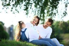 Αναμένοντες γονείς και η μικρή συνεδρίαση κορών τους στη χλόη Στοκ εικόνα με δικαίωμα ελεύθερης χρήσης