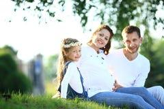 Αναμένοντες γονείς και η μικρή συνεδρίαση κορών τους στη χλόη Στοκ φωτογραφία με δικαίωμα ελεύθερης χρήσης