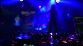 Αναμίκτης ελεγκτών του DJ στο νυχτερινό κέντρο διασκέδασης με τη θολωμένη σκιαγραφία του χορεύοντας τραγουδιστή κοριτσιών φιλμ μικρού μήκους