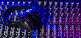 Αναμίκτης του DJ με τα ακουστικά σε ένα νυχτερινό κέντρο διασκέδασης Στοκ Φωτογραφία