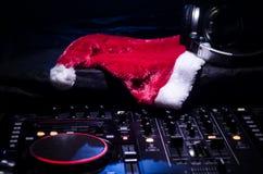 Αναμίκτης του DJ με τα ακουστικά στο σκοτεινό υπόβαθρο νυχτερινών κέντρων διασκέδασης με τη νέα παραμονή έτους χριστουγεννιάτικων στοκ εικόνα