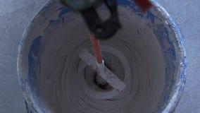 Αναμιγνύοντας το μίγμα με έναν αναμίκτη σε ένα τρυπάνι - σε αργή κίνηση απόθεμα βίντεο