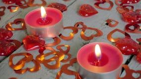Αναμμένα επάνω κεριά στον ξύλινο πίνακα με τις κόκκινες καρδιές γύρω κόκκινος αυξήθηκε απόθεμα βίντεο
