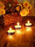 Αναμμένα κεριά και ένα ψάθινο καλάθι με μια κολοκύθα και λουλούδια στο υπόβαθρο Στοκ εικόνα με δικαίωμα ελεύθερης χρήσης