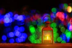 Αναμμένο κερί φανάρι μπροστά από τα φω'τα Χριστουγέννων Στοκ Εικόνες