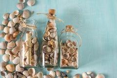 Αναμνηστικά όπως μπουκάλια με τα θαλασσινά κοχύλια εσωτερικό μικρό λευκό ποικιλίας διακοσμήσεων ανασκόπησης άρθρων Στοκ Εικόνα
