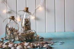 Αναμνηστικά όπως μπουκάλια με τα θαλασσινά κοχύλια εσωτερικό μικρό λευκό ποικιλίας διακοσμήσεων ανασκόπησης άρθρων Στοκ εικόνες με δικαίωμα ελεύθερης χρήσης