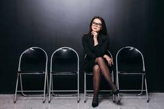 αναμονή γραμμών Βέβαια νέα συνεδρίαση επιχειρηματιών στην καρέκλα στο μαύρο κλίμα Στοκ Εικόνα