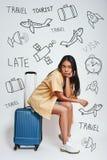 αναμονή πτήσης Πλήρες μήκος της αρκετά ασιατικής συνεδρίασης γυναικών στις αποσκευές της και της αναμονής για μια πτήση στεμένος στοκ εικόνα