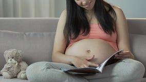 Αναμονή της θηλυκής συνεδρίασης στον καναπέ και το περιοδικό ανάγνωσης, στήλη για τη μελλοντική μητέρα απόθεμα βίντεο