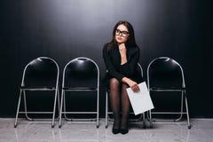 Αναμονή τη συνέντευξη Βέβαιο νέο έγγραφο εκμετάλλευσης επιχειρηματιών καθμένος στην καρέκλα στο μαύρο κλίμα Στοκ εικόνα με δικαίωμα ελεύθερης χρήσης