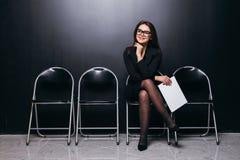 Αναμονή τη συνέντευξη Βέβαιο νέο έγγραφο εκμετάλλευσης επιχειρηματιών καθμένος στην καρέκλα στο μαύρο κλίμα Στοκ Φωτογραφία