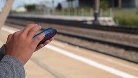 Αναμονή το τραίνο και χρησιμοποίηση του κινητού τηλεφώνου απόθεμα βίντεο