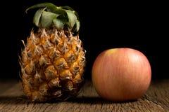 ανανάς και μήλο σε ξύλινο Μαύρη ανασκόπηση Στοκ Εικόνες