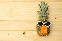 Ανανάς μόδας με τα γυαλιά ηλίου στο smartphone στον ξύλινο πίνακα στοκ εικόνες με δικαίωμα ελεύθερης χρήσης