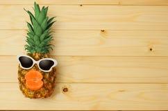 Ανανάς μόδας με τα γυαλιά ηλίου στο smartphone στον ξύλινο πίνακα στοκ φωτογραφίες