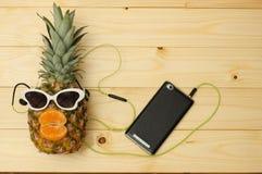 Ανανάς μόδας με τα γυαλιά ηλίου στο smartphone στον ξύλινο πίνακα στοκ εικόνες