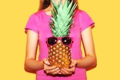 Ανανάς μόδας με τα ρόδινα γυαλιά ηλίου στη γυναίκα χεριών πέρα από κίτρινο Στοκ εικόνες με δικαίωμα ελεύθερης χρήσης