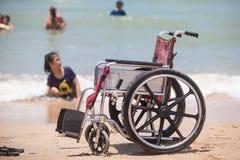 Αναπηρική καρέκλα στην παραλία με τα άτομα με ειδικές ανάγκες που κολυμπούν στη θάλασσα Στοκ Φωτογραφία