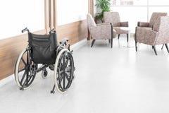 Αναπηρική καρέκλα που σταθμεύουν κενή στο διάδρομο νοσοκομείων στοκ φωτογραφία