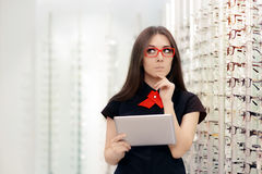 Αναποφάσιστη γυναίκα με την ταμπλέτα PC στο οπτικό κατάστημα Στοκ Εικόνες
