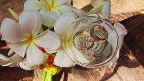 Αναποδογυρισμένα γαμήλια δαχτυλίδια γυαλιού κρασιού στην κορυφή από τα άσπρα λουλούδια απόθεμα βίντεο