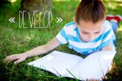 Αναπτυχθείτε ενάντια στη χαριτωμένη ανάγνωση μικρών κοριτσιών στο πάρκο στοκ εικόνες