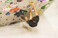 Αναρρίχηση βράχου άσκησης ατόμων στον τεχνητό τοίχο στο εσωτερικό ηθοποιών στοκ εικόνες