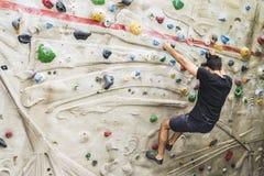 Αναρρίχηση βράχου άσκησης ατόμων στον τεχνητό τοίχο στο εσωτερικό ηθοποιών στοκ εικόνα με δικαίωμα ελεύθερης χρήσης